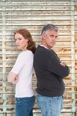 stock photo of not talking  - Casual couple not speaking after fight against wooden background in pale wood - JPG