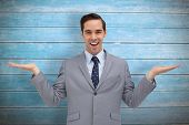 stock photo of presenting  - Smiling businessman presenting something with his hands against wooden planks - JPG