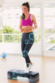 picture of step aerobics  - Full length of a fit woman performing step aerobics exercise against fitness interface - JPG