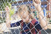 stock photo of playground school  - A sad little girl at school playground - JPG