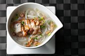 stock photo of crispy rice  - Closeup top down view of Thai style crispy pork rice noodle soup in a bowl with copy space - JPG