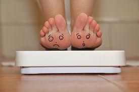 stock photo of sad  - Feet on bathroom scale with hand drawn sad cute faces - JPG