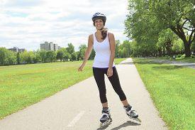image of inline skating  - A Roller skating girl in park rollerblading on inline skates - JPG