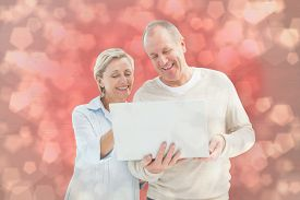 image of male pattern baldness  - Happy mature couple using laptop against light glowing dots design pattern - JPG