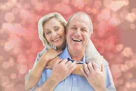 foto of male pattern baldness  - Happy mature couple embracing smiling at camera against light glowing dots design pattern - JPG
