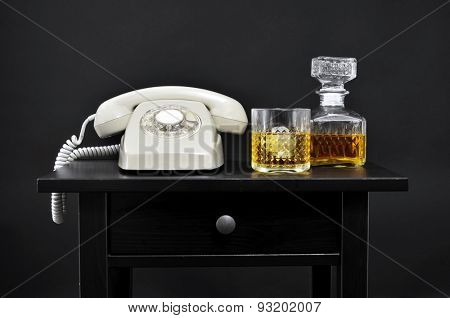 a retro beige rotary dial telephone, and a bottle and a lowball glass with liquor on a black table, over a black background