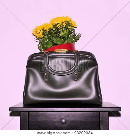 yellow chrysanthemum flowers in a vintage leather bag on a black table, with a retro snapshot effect