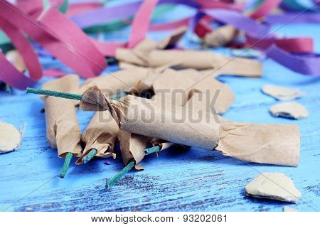 some firecrackers, and confetti and streamers of different colors on a rustic blue wooden surface