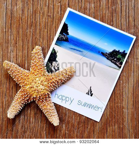 high-angle shot of a starfish and an instant photo of a peaceful beach with the text happy summer written in its frame, placed on a rustic wooden surface