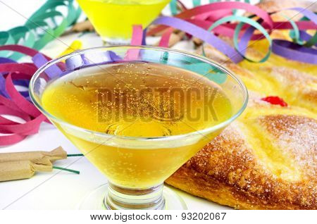closeup of two glasses with champagne, some firecrackers and streamers, and a coca de Sant Joan, a typical sweet flat cake from Catalonia, Spain eaten on Saint Johns Eve