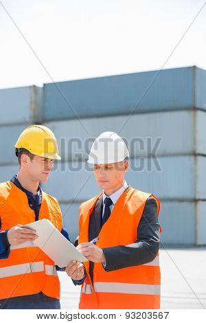 Worker taking sign of supervisor on clipboard in shipping yard