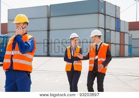 Worker using walkie-talkie while colleagues discussing in shipping yard