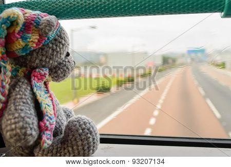 grey knited travel toy bear sit nera window in HongKong bus