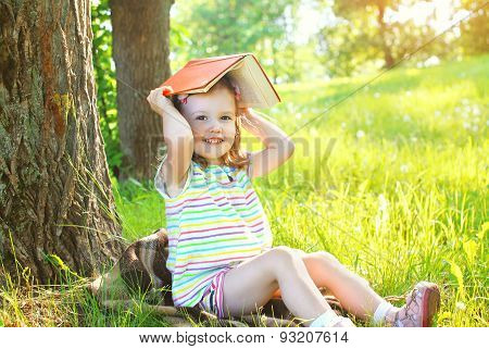 Little Smiling Girl Child With Book Playing On The Grass In Sunny Summer Day