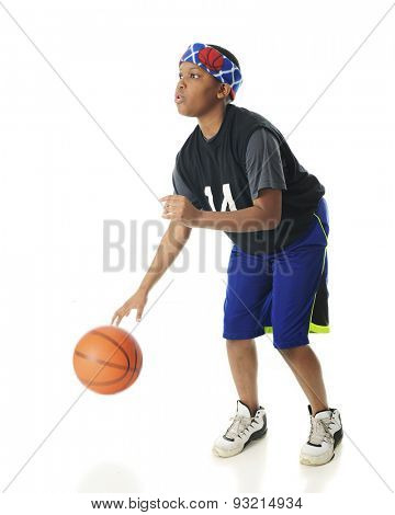 A young athlete focused on the the hoop as he rapidly dribbles his basketball.  Motion blur on his hand and the ball.  On a white background.