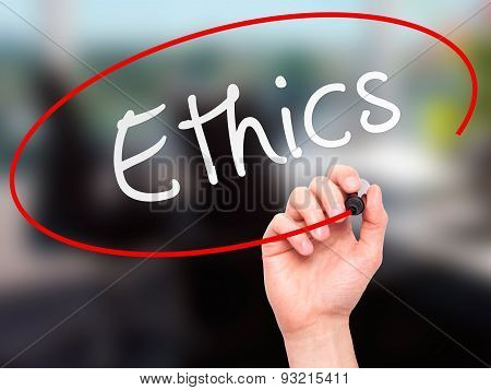 Man hand writing Ethics on visual screen.