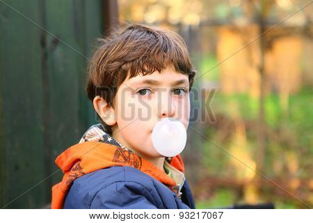 Preteen Handsome Boy With Chewing Gum Bubble Close Up Counrty Portrait