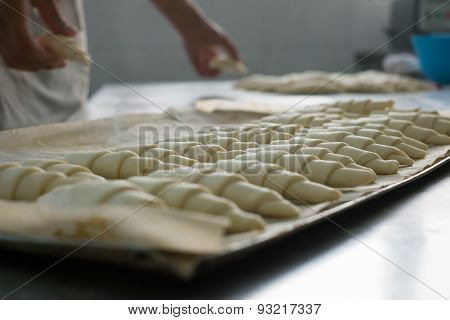 Baker Putting Unbaked Croissants Onto Tray