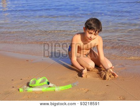 Preteen Handsome Boy With Snorkeling Mask And Tube Build Castle From Sand On The Red Sea Background