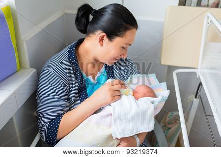 Mother feeding her adorable daughter in the hospital