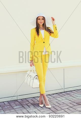 Beautiful Young Woman In Yellow Suit Clothes And Hat With Handbag Outdoors, Street Fashion