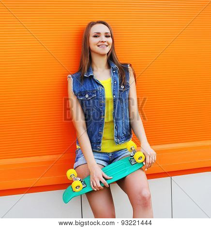 Fashion Portrait Of Hipster Girl In Colorful Clothes With Skateboard Having Fun Against The Orange W