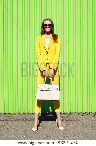 Fashion Pretty Woman In Yellow Suit Clothes With Handbag Posing Against The Colorful Green Wall