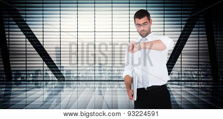 Serious businessman holding laptop checking time against room with large window looking on city