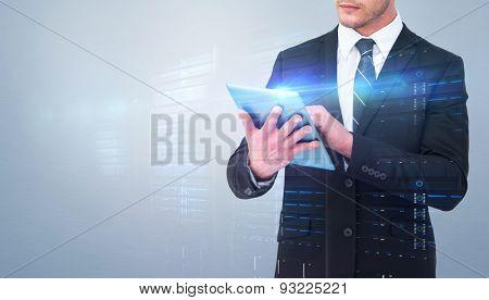 Unsmiling businessman using tablet pc against grey vignette
