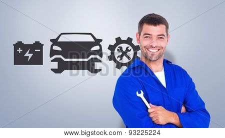 Happy mechanic holding spanner on white background against grey vignette