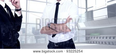 Smiling businessman with arms crossed against airport terminal