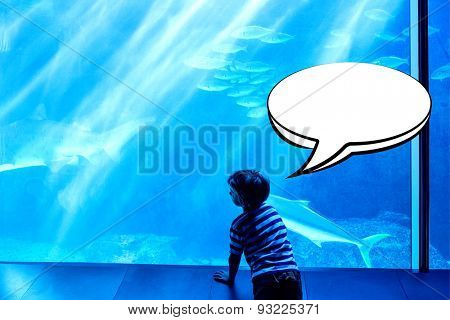 Speech bubble against young man looking at fish in a giant tank