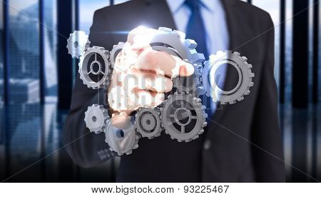 Businessman pointing his finger at camera against room with large window looking on city