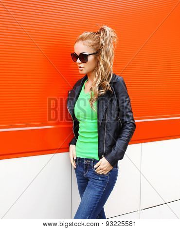Fashion Pretty Woman In Rock Black Style, Wearing A Sunglasses And Leather Jacket Standing Against T