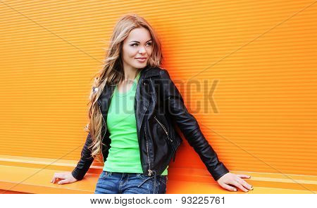 Portrait Of Beautiful Blonde Woman Wearing A Black Rock Leather Jacket Against The Colorful Orange W