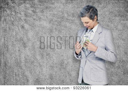 Businesswoman taking bribe against grey background