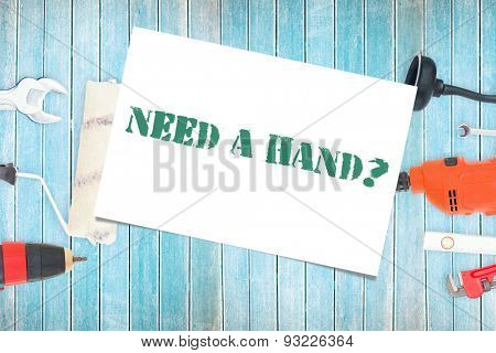 The word need a hand? and white card against diy tools on wooden background