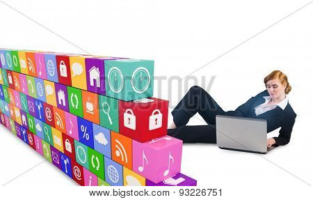 Redhead businesswoman using her laptop against wall of apps