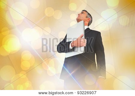 Businessman in suit holding his laptop proudly against yellow abstract light spot design