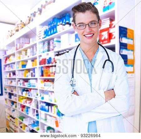 Doctor with arms crossed smiling at camera against close up of shelves of drugs