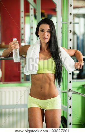 Fit woman leaning on weight bar with bottle of water and towel resting after hard training for bikin