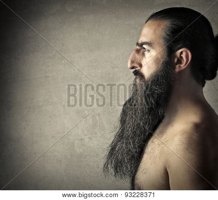 Naked man with a long dark beard