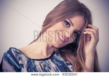 Smiling teenage girl with hand in her hair