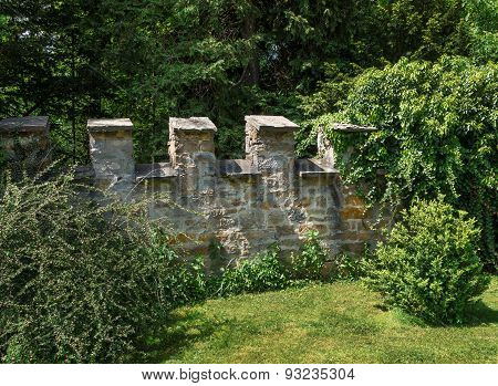 Castle wall with battlement in a garden