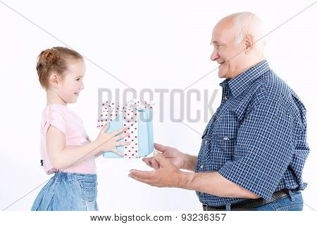 Granddaughter making a present to grandfather