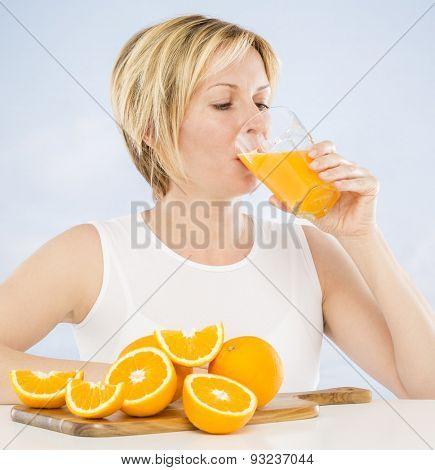 Forty years woman drinking juice