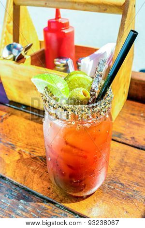 Caesar or bloody mary cocktail drink rimmed with spice and garnished with lime wedge pepper and oliv