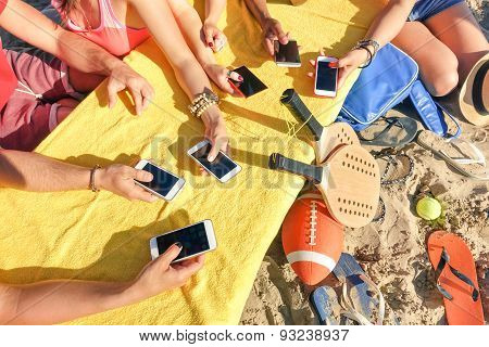 Hands in Group Of Multiracial Friends Having Fun Together With Mobile Smartphones
