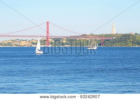 Sailing on the river Tejo with the 25 Abril bridge and the Christo Rei in Lisbon Portugal