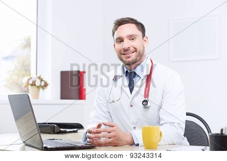 Smiling cardiologist sitting at the table
